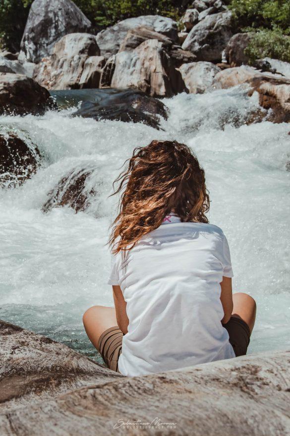 Una donna guarda l'impetuoso fiume verzasca